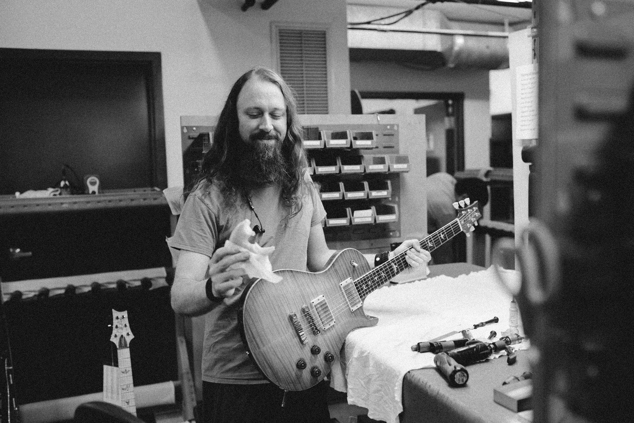 PRS employee enjoys a donut while next to a guitar